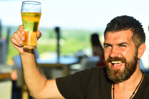 Photo of a man cheersing with a beer