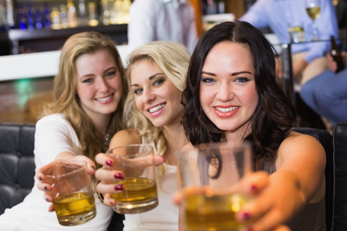 Women sharing a whiskey drink